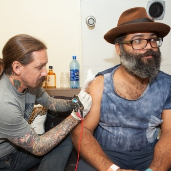 Kyp Malone of TV On The Radio getting an Oliver Peck tattoo at FYF FEST