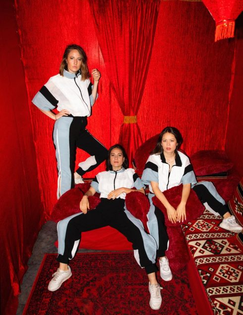 Haiku Hands red background wearing jumpsuits